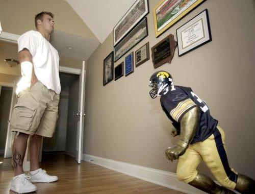 Matt Roth a senior at looks at a wall of personal memorabilia in his bedroom at the family home in Oak Brook, Ill., Friday, August 6, 2004. The figure of a football player was a gift from his mother on his 21st birthday. (AP Photo/Stephen J. Carrera)