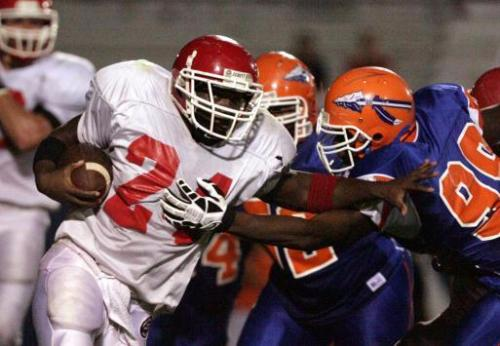 Caption: Northeast High School's Jeff Brinson, left, shoves Southeast High School defender Giovani Francois out of the way during an 80-yard touchdown run in a 2007 game.