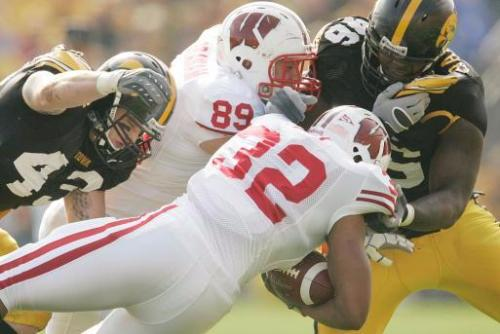Caption: Iowa's Pat Angerer (left, 43) tackles Wisconsin's John Clay (32) as Garrett Graham (89) stuggles with Iowa's Christian Ballard (right, 46) during the first quarter at Kinnick Stadium on October 18, 2008. The Hawkeyes won, 38-16. (Gazette photo)
