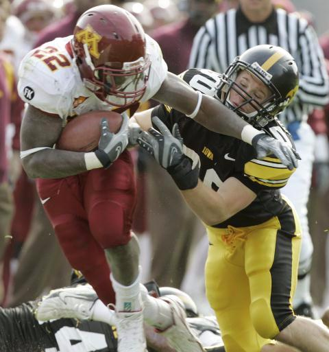 Minnesota's Duane Bennett, left, tries to break a tackle by Iowa's Brett Greenwood during the first half of a football game, Saturday, Nov. 10, 2007, in Iowa City, Iowa. Greenwood has been a target of dissatisfied internetters for awhile. Let's hug it out on this, people. (AP Photo/Charlie Neibergall)