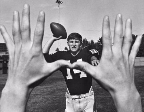 Caption: Iowa Hawkeye Football History. Little caption information available. Photo appears to show Iowa quarterback Ed Podolak (#14) showing his passing accuracy in front of the photographer before the 1967 season. Podolak played quarterback for Iowa in 1966, 1967 and the first part of 1968, after which he switched to running back. The 1967 Hawkeye team went 1-8-1 overall, and 0-6-1. (Gazette file)