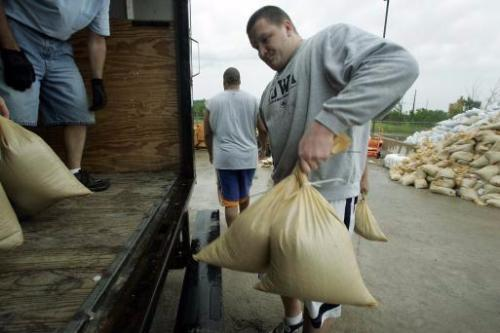 University of Iowa football offensive lineman Bryan Bulaga loads sandbags in to a truck at the Coralville, Iowa, Streets Department facility on Wednesday, June 11, 2008. Floodwaters in the Iowa City, Iowa and Coralville area continue to rise as more water pours over the emergency spillway at the Coralville Lake. (AP Photo/The Gazette, Brian Ray)