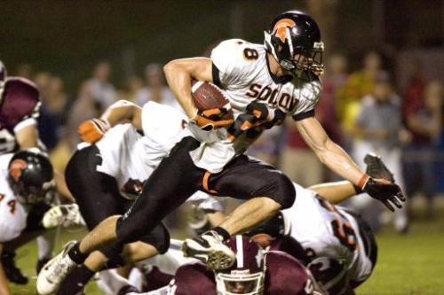 Solon's James Morris carries the ball over Mount Vernon defense players during their game Friday, Aug. 29, 2008 at Mount Vernon. (Gazette file)