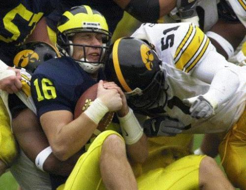 Michigan quarterback John Navarre (16) is sacked by Iowa's Howard Hodges, left, and Fred Barr (51) in the second quarter Saturday, Oct. 26, 2002, in Ann Arbor, Mich. Navarre was sacked five times in Michigan's 34-9 loss to Iowa. (AP Photo/Carlos Osorio)