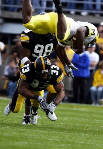 Michigan runningback Chris Perry (23) is sent airborne after collididing with Iowa's Bob Sanders (33) during the first quarter of the game on Saturday October 4, 2003 at Kinnick Stadium in Iowa City. (Cliff Jette/Gazette)