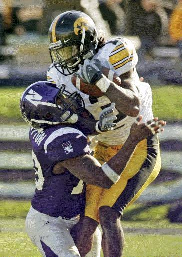 Caption: Iowa's Charles Godfrey, right, intercepts a pass intended for Northwestern's Tyrell Sutton during the fourth quarter of a football game Saturday, Nov. 3, 2007, in Evanston, Ill. Iowa won 28-17. (AP Photo/Jerry Lai)
