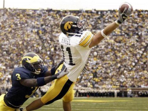 Caption: Iowa's Ed Hinkel (11) pulls in his first quarter touchdown reception over Michigan's Jackson Marlin (3) during their game Saturday September 25, 2004 at Michigan Stadium in Ann Arbor, Mich. (Gazette/Brian Ray)
