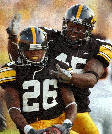 Caption: Iowa's Jovon Johnson, left, celebrates with teammate Jonathan Babineaux, right, after making an interception during the first half against Arizona State, Saturday Sept. 20, 2003, in Iowa City, Iowa. (AP Photo/Charlie Neibergall)